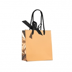 Rose-gold mirror-effect paper boutique bag with black rope handles and ribbon fastener